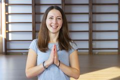 Young woman doing yoga on the rug in the hall royalty free stock photography
