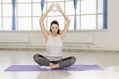 Young woman doing yoga on the rug in the hall royalty free stock photo