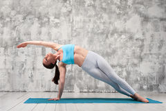 Young woman doing yoga side plank position indoors stock photography