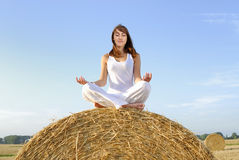Young woman doing yoga on a straw bale Royalty Free Stock Photo