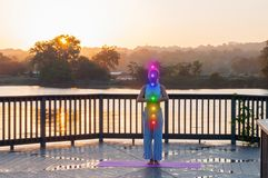 Young woman is doing yoga on the sunrise. Woman is meditating with glowing seven chakras outdoors. Beautiful  woman is practicing yoga on the lake stock images