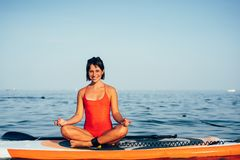 Young woman doing yoga on sup board with paddle. Meditative pose stock images