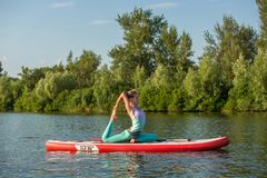 Young woman doing yoga on sup board with paddle. Meditative pose, side view - concept of harmony with the nature. Free and healthy living, freelance, remote royalty free stock photos