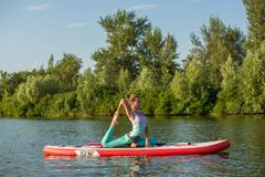 Young woman doing yoga on sup board with paddle. Meditative pose, side view - concept of harmony with the nature. Free and healthy living, freelance, remote stock image
