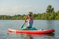 Young woman doing yoga on sup board with paddle. Meditative pose, side view - concept of harmony with the nature. Free and healthy living, freelance, remote royalty free stock images