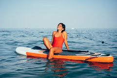 Young woman doing yoga on sup board with paddle. Meditative pose stock photo
