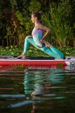 Young woman doing yoga on sup board with paddle. Yoga pose, side view - concept of harmony with the nature. Young woman doing yoga on sup board with paddle stock photo