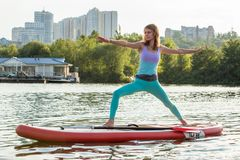 Young woman doing yoga on sup board with paddle. Yoga pose, side view - concept of harmony with the nature. Young woman doing yoga on sup board with paddle royalty free stock photography