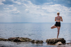 Young Woman doing Yoga Tree Position. In Front of the Ocean stock photos