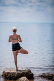 Young Woman doing Yoga Tree Position. In Front of the Ocean royalty free stock photo
