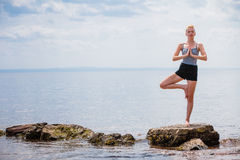 Young Woman doing Yoga Tree Position. In Front of the Ocean royalty free stock image