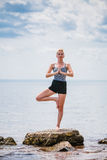 Young Woman doing Yoga Tree Position. In Front of the Ocean royalty free stock photos