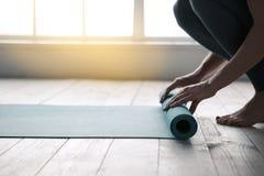 Young Woman Doing Yoga Twist Mat Healthy Lifestyle. Young woman doing yoga twisting mat indoors near window stock photography