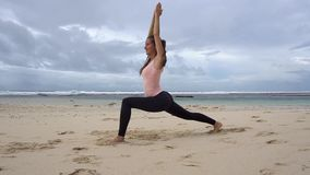 Woman doing yoga warrior pose on coast of ocean on beach. Young woman doing yoga warrior pose on coast of ocean on beach stock video