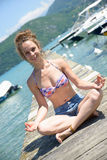 Young woman doing yoga on the waterside Royalty Free Stock Image