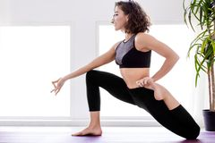 Young woman doing yoga workout at home. Young female is standing at half frog pigeon pose. Athletic woman in black uniform is practicing yoga, meditating in stock photos