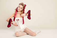 Young woman  in the doll style with red bow and red high-heeled. Young woman  in the doll style with red bow and red shoes  sitting on the floor Royalty Free Stock Photos