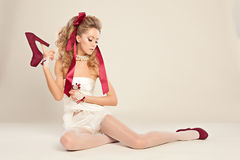 Young woman  in the doll style. With red bow and red shoes  sitting on the floor Royalty Free Stock Photos