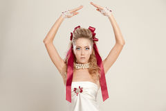 Young woman in a doll style with red bows, holding her hands up Royalty Free Stock Image