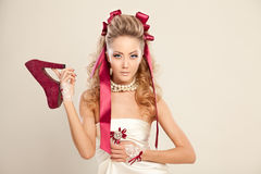 Young woman in a doll style with red bows, holding a red high-he. Young woman in a doll style with red bows, holding a red shoe. Studio photography Stock Photos