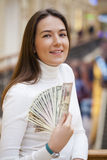 A young woman with dollars in her hands. A young brunette woman with dollars in her hands, indoor Stock Images