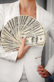 A young woman with dollars in her hands, isolated on white. Business woman holding a bunch of money and board stock photo