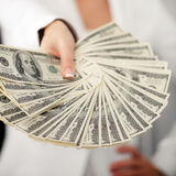 A young woman with dollars in her hands, isolated on white. Business woman holding a bunch of money and board stock photography