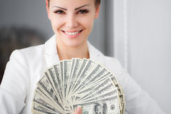 A young woman with dollars in her hands, isolated on white. Business woman holding a bunch of money and board royalty free stock image