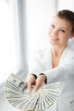 A young woman with dollars in her hands, isolated on white. Business woman holding a bunch of money and board royalty free stock photography