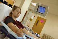 Young woman donating platelets. Young woman sitting in chair with needle in her arms donating platelets Stock Photo