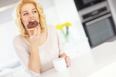 Young woman with donut and coffee in the kitchen Royalty Free Stock Photo