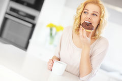 Young woman with donut and coffee in the kitchen Stock Image