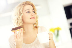 Young woman with donut and coffee in the kitchen Royalty Free Stock Images