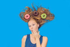 Young woman with donuts in her hair. Multicolored donuts. Harm of sweet.  Stock Image