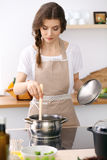Young woman in a dotted biege apron cooking soup in the kitchen. Food and health concept Royalty Free Stock Photos
