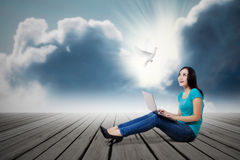 Young woman with dove and laptop. Asian female student looking at dove with laptop outdoor royalty free stock photo