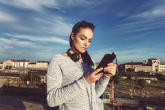 Young woman downloading music on tablet outdoor Stock Images