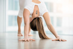 Young woman in Downward facing dog pose against floor window. Young woman practicing yoga, stretching in adho mukha svanasana exercise, Downward facing dog pose stock image