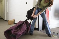 Young woman dragging a bag royalty free stock photography