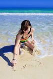 Young woman drawing in the beach sand Royalty Free Stock Images