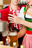 Young woman drawing beer in restaurant or pub Stock Images