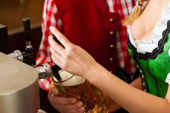 Young woman drawing beer in restaurant or pub Royalty Free Stock Photo
