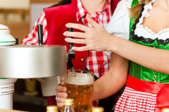 Young woman drawing beer in restaurant or pub. She is the innkeeper stock photo