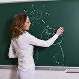 Young woman is drawing on a blackboard. Young woman is drawing a picture on a blackboard, positive, in profile Royalty Free Stock Image
