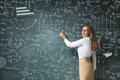 Young woman drawing charts and graphs on blackboard Royalty Free Stock Photography