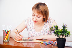 Young woman drawing at the desk Royalty Free Stock Photos