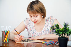 Young woman drawing at the desk Royalty Free Stock Image