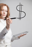 Young woman drawing dollar symbol Royalty Free Stock Photography