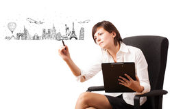 Young woman drawing famous cities and landmarks on whiteboard. Isolated on white Royalty Free Stock Photos