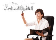 Young woman drawing famous cities and landmarks on whiteboard Stock Images